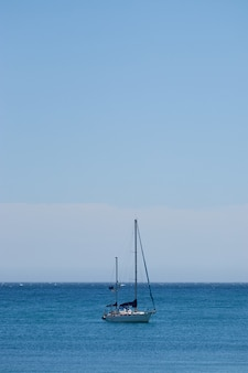 Vertical shot of a small boat sailing in the ocean with a clear blue sky