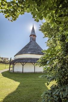 Colpo verticale di una piccola chiesa dietro gli alberi nella campagna della slovenia