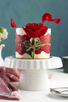 Vertical shot of a small fancy cake with a red rose on a white tray
