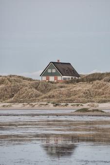 Colpo verticale di una piccola casa isolata sulla riva del mare