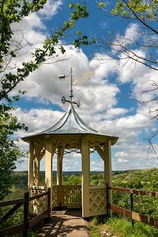 Colpo verticale di una piccola torre di fronte a una foresta sotto un cielo nuvoloso