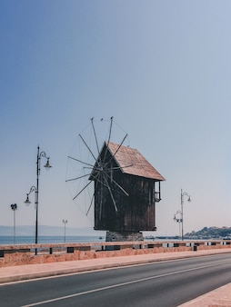 Vertical shot of a small wooden windmill on the side of the road in the countryside