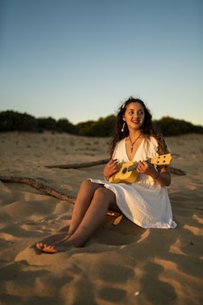 Vertical shot of a smiling female in a white dress sitting on a sandy ground