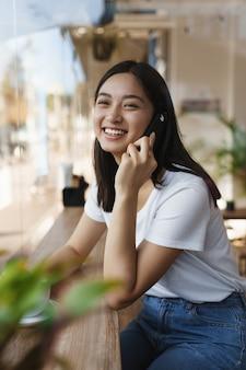 Colpo verticale sorridente, millenaria ragazza asiatica carina nella caffetteria, parlando tramite smartphone.