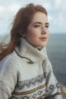 Colpo verticale di una donna sorridente con il mare sul