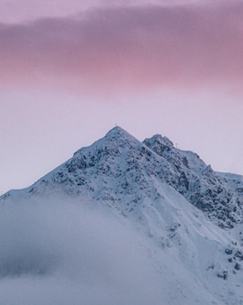 Colpo verticale del picco di montagna innevato sotto il cielo nuvoloso variopinto