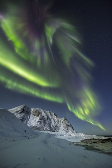 Vertical shot of the snow covered mountains under the beautiful northern lights in the sky