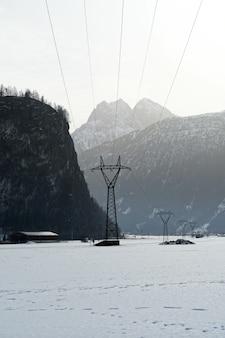 Colpo verticale delle montagne innevate in inverno in una giornata nebbiosa