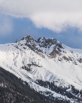 Vertical shot of the snowy peaks of the mountains under the cloudy sky