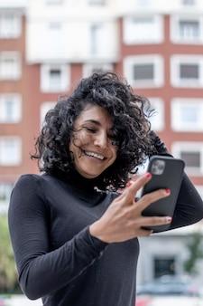 Ripresa verticale di una donna spagnola che sorride mentre usa il telefono