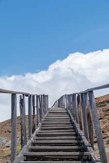 Vertical shot of a staircase leading to the mountains touching the sky in galapagos islands, ecuador