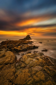 Vertical shot of the stones at the seaside under the fantastic sunrise