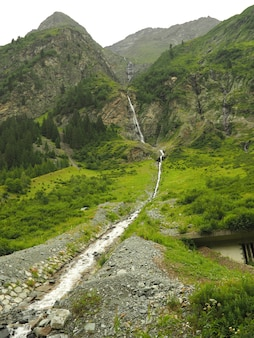 Vertical shot of a stream flowing water with green mountains