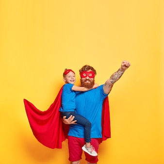 Vertical shot of strong red haired man in superhero costume, raises fist and makes flying gesture