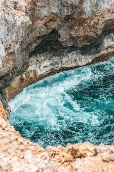 Colpo verticale di forti onde del mare che colpiscono la scogliera