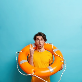 Vertical shot of stunned man holiday maker poses with inflated lifebuoy uses safety equipment