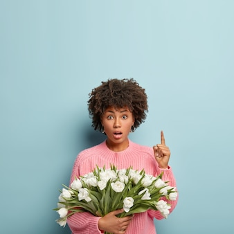 Vertical shot of stupefied afro american lady points above with fore finger, has bated breath, holds nice bouquet of white spring tulips, wears casual pink jumper, isolated against blue wall