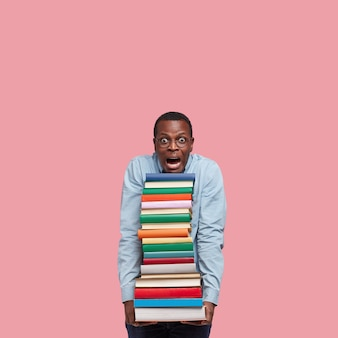 Vertical shot of stupefied black man leans head on pile of books, wears round glasses, surprised with many tasks for seminar