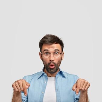 Il colpo verticale del maschio caucasico stupefatto indica verso il basso, mostra qualcosa, vestito in camicia blu casuale, isolato sopra il muro bianco