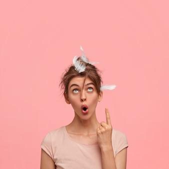 Colpo verticale della donna assonnata stupefatta con la piuma sulla testa, ha un'espressione facciale stupita, punta verso l'alto