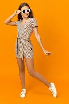 Colpo verticale di giovane donna alla moda alla moda con pelle abbronzata, gambe lunghe e sottili in posa in studio arancione