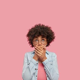 Colpo verticale della donna afroamericana sorpresa copre la bocca con entrambe le mani, cerca di essere senza parole, guarda con espressione scioccata verso l'alto, nota qualcosa di strano, isolato sopra il muro bianco rosa