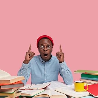 Colpo verticale dell'uomo di colore sorpreso con espressione stupita, punta con entrambi gli indici al soffitto, indossa abiti alla moda
