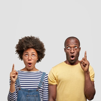 Vertical shot of surprised dark skinned african american female and male point upwards, have stunned expressions, keep jaw dropped