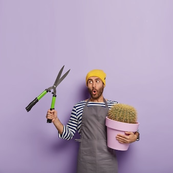 Vertical shot of surprised male gardener holds pruning shears