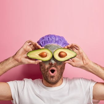 Vertical shot of surprised man holds avocado slices on eyes for skin care procedure, applies beauty clay mask, uses healing properties of fruit