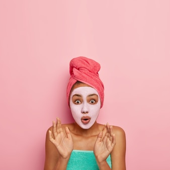 Vertical shot of surprised young female raises hands from fear, afraids of looking old, reduces wrinkles, applies special rejuvenating mask, has eyes popped out, wrapped towel on head