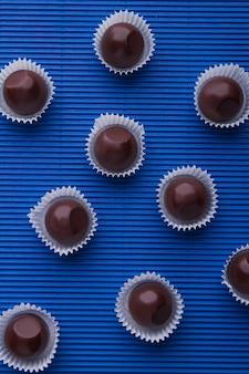 Вертикальный выстрел сладкие коричневые шоколадные конфеты на синем фоне