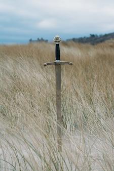 Vertical shot of a sword in the sandy beach