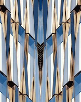 Vertical shot of a symmetrical blue glass and concrete building