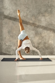 Vertical shot of tanned athletic young man working out in gym doing variation of standing split or urdhva prasarita eka padasana against grey wall. fit sporty guy practicing advanced yoga indoors