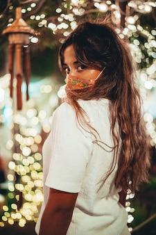 Colpo verticale di donna europea abbronzata che indossa una maschera floreale in un parco di divertimenti