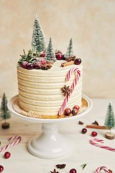 Colpo verticale di una gustosa torta di natale con bastoncini di zucchero e abeti