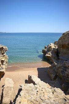 Colpo verticale di therocks sulla riva del mare presso la spiaggia pubblica di playa illa roja in spagna