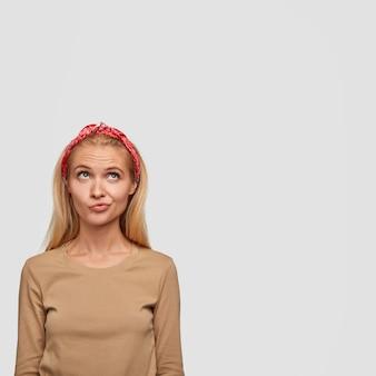 Colpo verticale di donna europea confusa premurosa con capelli lisci chiari, guarda verso l'alto, stringe le labbra, contempla qualcosa