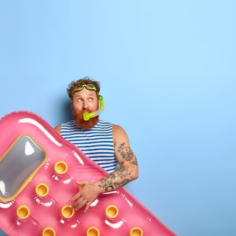 Vertical shot of thoughtful redhead guy wears snorkeling mask, enjoys swimming and resting, holds pink inflated mattress