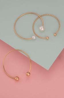 Vertical shot of three golden bracelets on pastel colors background