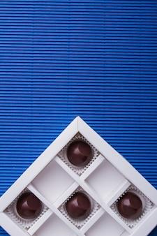 Вертикальный выстрел вид сверху шоколадные конфеты на синем фоне