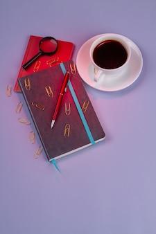 ペンとコピーブック付きの垂直ショット上面図コーヒーカップ。紫色の背景に分離。