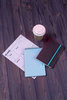 Vertical shot top view notepad with plastic cup of coffee.