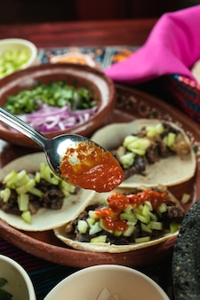 Vertical shot of tortillas with meat seen through tomato sauce spoon