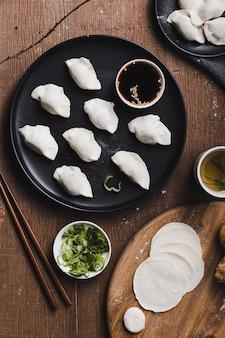 Colpo verticale di gnocchi di cinese tradizionale con le bacchette su un tavolo di legno