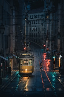Vertical shot of a tramway as it passes through the buildings of a city during nighttime