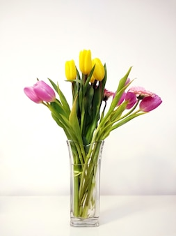 Vertical shot of a tulip bouquet in a vase on the table under the lights