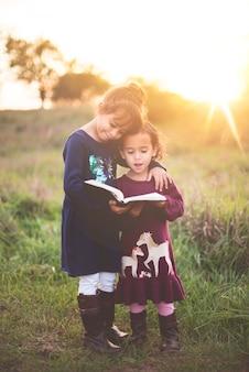 Ripresa verticale di due adorabili sorelline che leggono la bibbia al parco