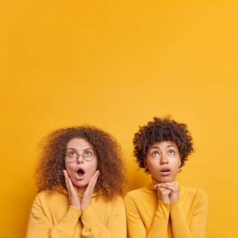 Vertical shot of two diverse women stare with shock above keeps mouth opened stand closely to each other dressed casually isolated over yellow  wall copy space for your promotion